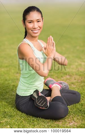 Portrait of smiling sporty woman doing the lotus pose in parkland