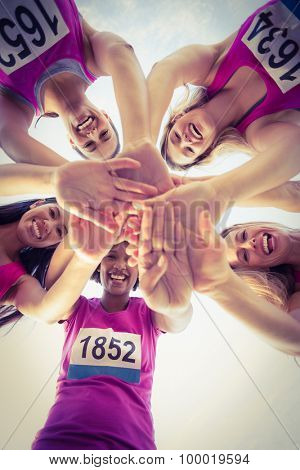 Portrait of five smiling runners supporting breast cancer marathon in parkland