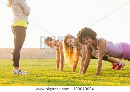 Portrait of smiling sporty women doing push ups during fitness class in parkland