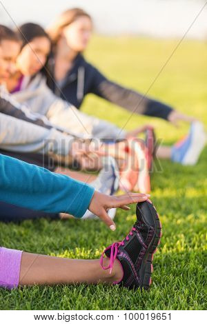 Sporty women stretching during fitness class in parkland