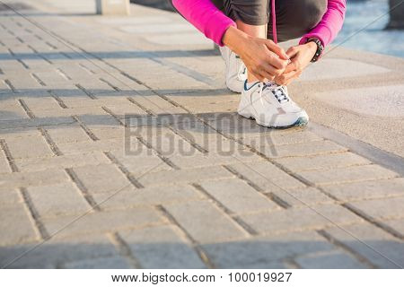 Sporty woman tying her shoelace at promenade on a sunny day