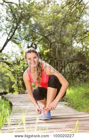 Portrait of Smiling blonde athlete tying shoelace on wooden trail in the nature