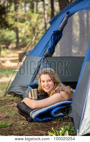 Portrait of pretty blonde camper smiling and lying in tent in the nature