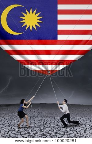 Two Workers Pulling Down Malaysian Flag