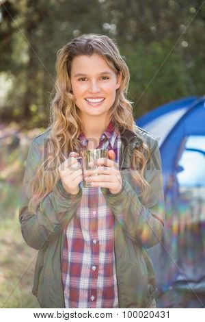 Portrait of smiling blonde camper standing in front of tent in the nature
