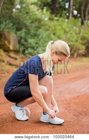 Athletic blonde tying her shoelace in the nature