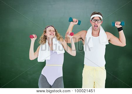 Geeky hipster couple lifting dumbbells in sportswear against green chalkboard