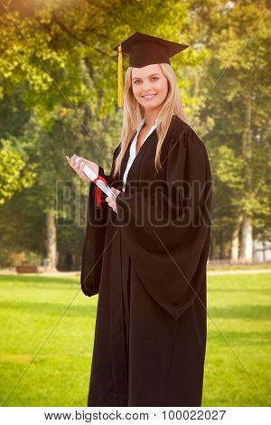 Blonde student in graduate robe holding a diploma against trees and meadow