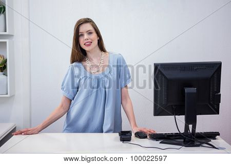 Shop worker standing by the till in fashion boutique