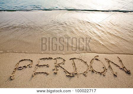 spanish word perdón written in the sand