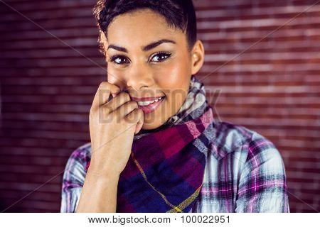 Portrait of a happy shy hipster against a red brick wall