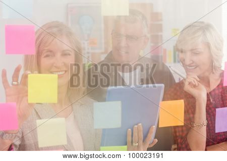 Business team working on tablet and sticky post its at office