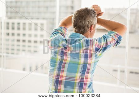 Rear view of troubled casual businessman leaning against window in the office