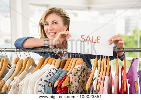 Portrait of smiling woman holding sale sign in clothing store