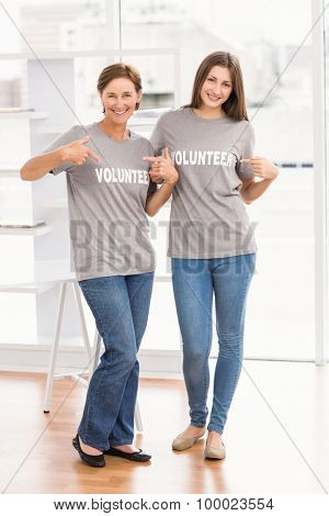 Portrait of smiling female volunteers showing their shirts in the office