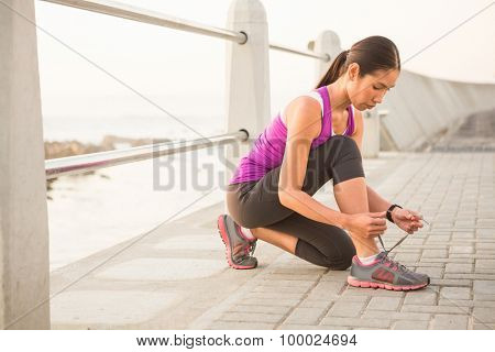 Fit woman tying shoelace at promenade on a sunny day