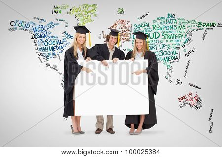 Three students in graduate robe holding and pointing a blank sign against grey vignette