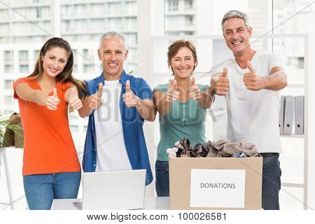 Portrait of casual business people donating and doing thumbs up in the office