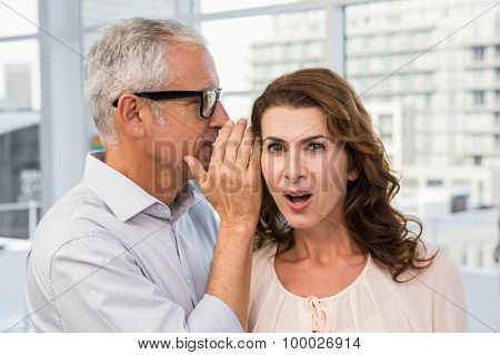Casual businessman whispering secret to his colleague in the office