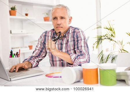 Thoughtful casual businessman sitting at working desk in the office