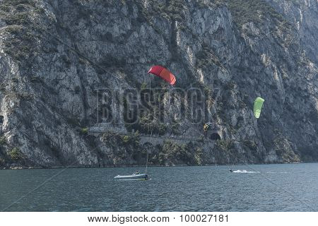 People in boats and on the water practicing sailing and sailing sports. Lake Garda