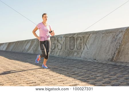 Sporty blonde jogging at promenade on a sunny day
