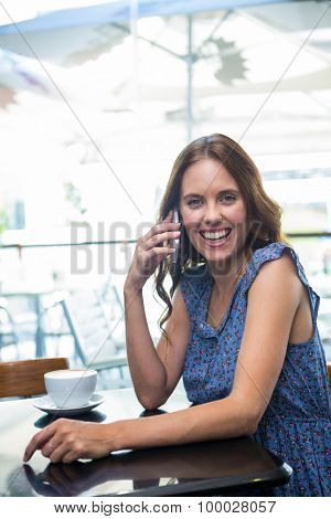 Woman having coffee and making a call in a coffee shop