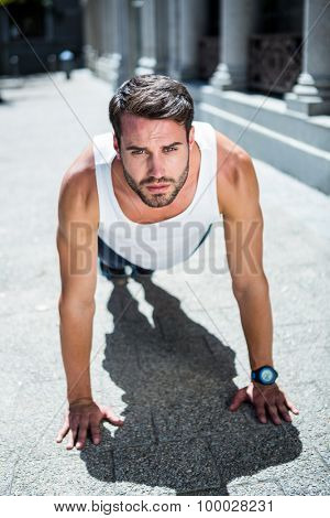 Portrait of handsome athlete doing push ups in the city