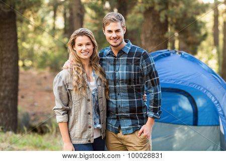 Happy young camper couple looking at the camera in the nature