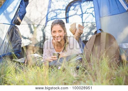 Smiling brunette camper lying in tent in the nature