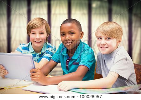 Cute pupils using tablet computer in library against window overlooking city