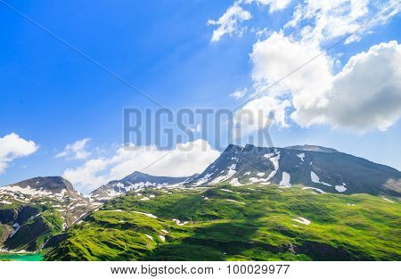 Beautiful Picture Of The Alpine Landscape With Snow And Green Meadows