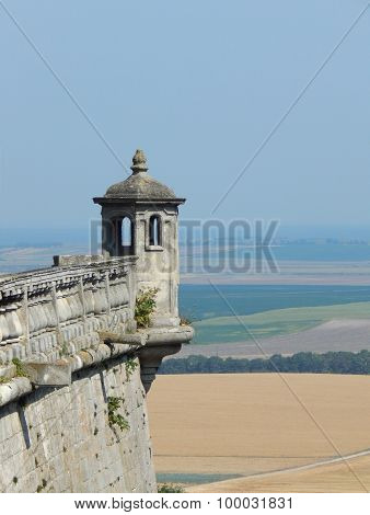 Small castle tower against the background of a beautiful landscape with fields