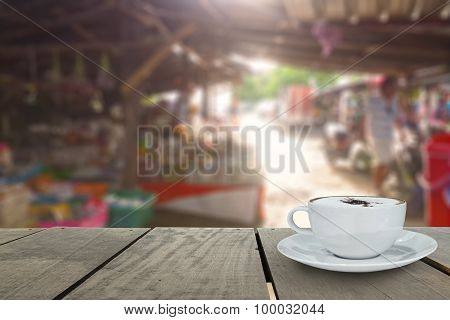 Coffee Cup On Terrace Wood And Local Market Blur Background