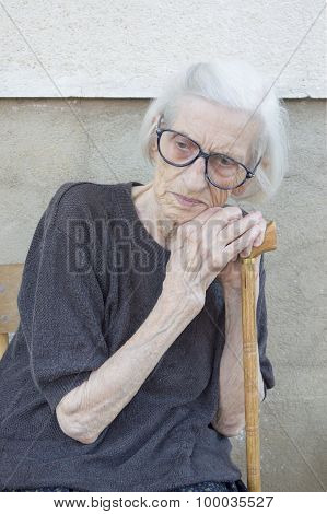 Portrait Of A Ninety Years Old Grandma Leaning On A Walking Stick Outdoors