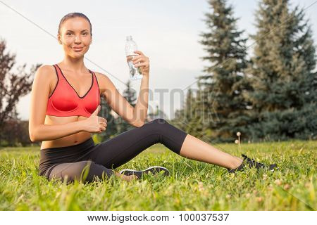 Attractive young sportswoman is drinking aqua after exercising