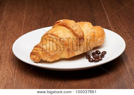 Fresh french croissant and coffee beans on white ceramic plate on dark wooden table