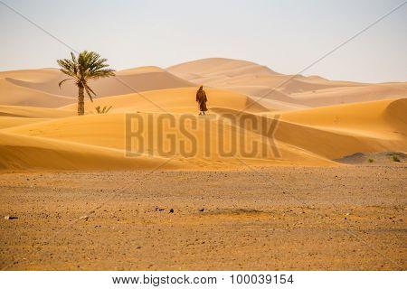 MERZOUGA, MOROCCO, APRIL 13, 2015: Local man walks on sand dunes