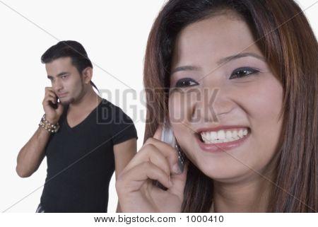 Pareja joven hablando por teléfonos móviles