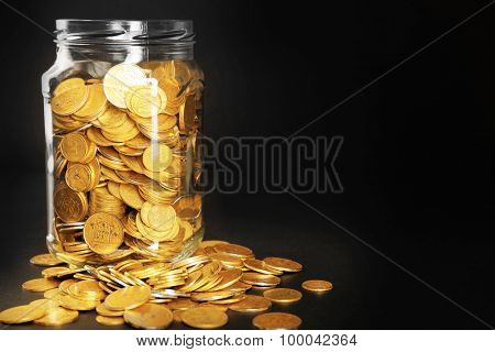 Glass jar with coins on dark background