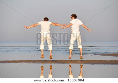 Two Friends Is Jumping At Morning Beach