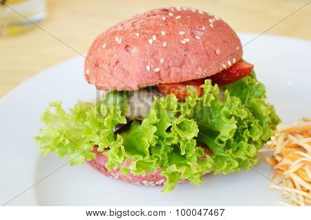 Tasty pink burger with meat, salad and strawberry