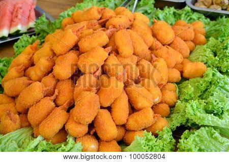 Breaded crab meat and claws on a big plate covered with lettuce salad