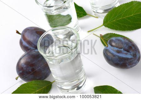 slivovitz (plum brandy) and fresh plums on white background