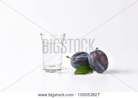 slivovitz (plum brandy) and fresh plum on white background