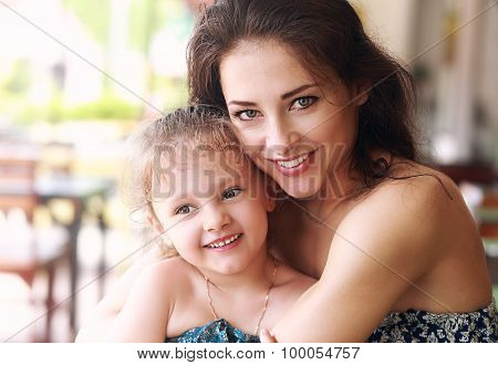 Happy Beautiful Mother Cuddling Her Daughter With Smile In Cafe. Closeup Portrait