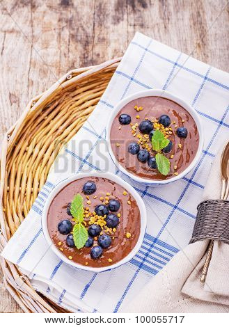 Chocolate banana pudding with topping of fresh forest blueberries and bee pollen