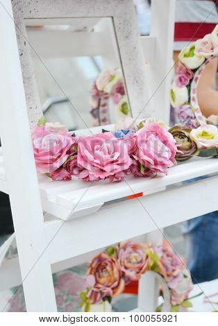 Wedding wreaths with roses and other flowers on white french shelf