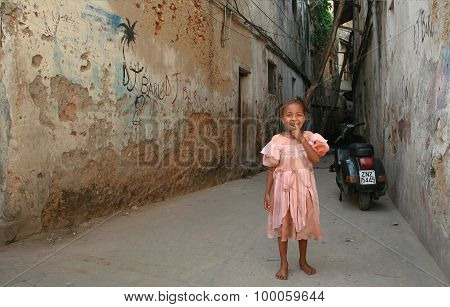 African Girl Smiling, Standing In A Courtyard Dilapidated Stone Houses.