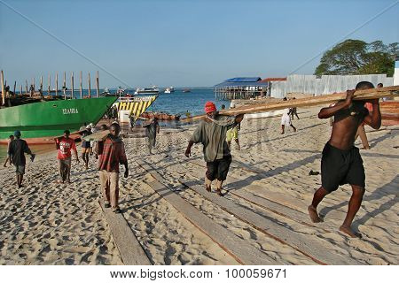 African Stevedores Unload Timber Ship In Port Of Zanzibar, Tanzania.